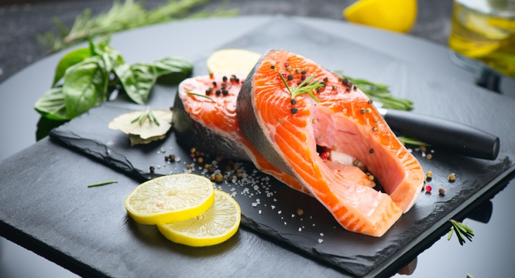 Salmon. Raw Trout Red Fish Steak served with Herbs and Lemon and